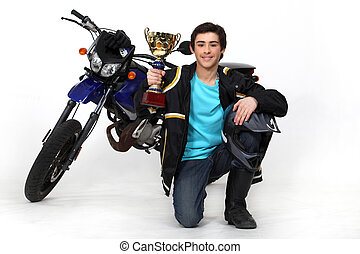 Teenager with gold cup in front of a motorbike