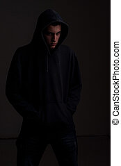 teenager with hoodie look on one side against a dirty dark gray
