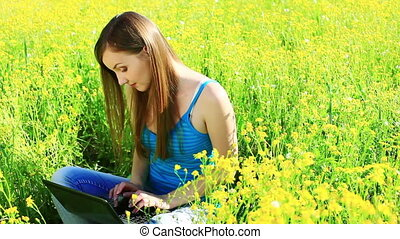 Teenager with laptop in the meadow