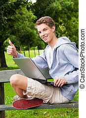 teenager with laptop outdoors - a teenager with a laptop...