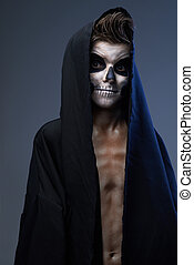 teenager with make-up of the skull in black cape