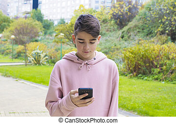 teenager with mobile phone on city street