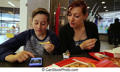 Teenager with Sister in Fast Food - A teenager with a woman...