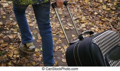 teenager with suitcase walking on pavement