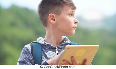 Teenager with Tablet Computer in Park