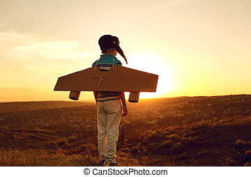 Teenager with toy airplane on nature at sunset