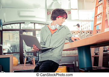 Teenager working with a laptop in the cafe
