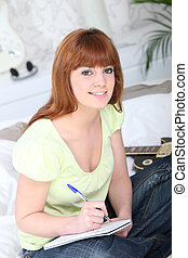 Teenager writing in notebook