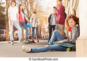 teenagerjunge, sitzen, auf, bürgersteig, mit, skateboard