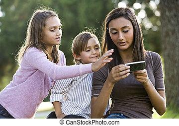 teenagermädchen, mit, handy, texting, jünger, geschwister,...