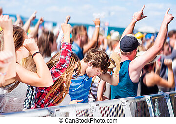 Teenagers at summer music festival having good time -...