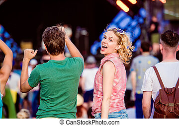 Teenagers at summer music festival dancing and singing -...