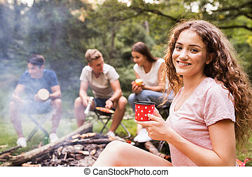 Teenagers camping, cooking meat on bonfire. - Beautiful...
