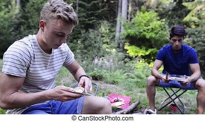 Teenagers camping, eating meat cooked on barbecue grill. -...
