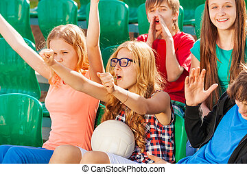 Teenagers cheer for team during game at stadium
