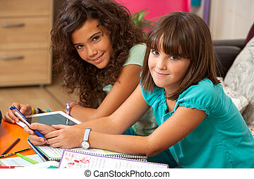 Two teenage girls doing homewotk at home.