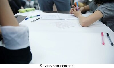 Teenagers draw with markers on a large sheet of paper,...