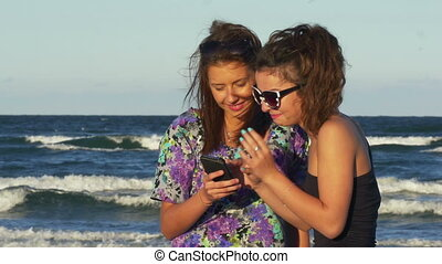 Teenagers excited when looking at a smart phone on the beach