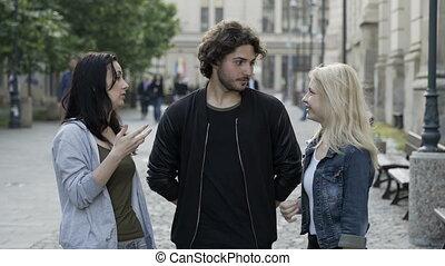 Teenagers friends talking outdoor in public urban street...