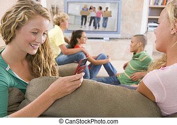 Teenagers Hanging Out In Front Of Television Using Mobile ...