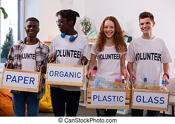 Teenagers holding boxes with different types of litter after sorting