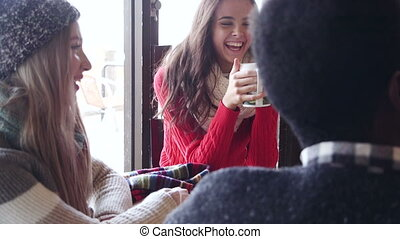 Teenagers In A Cafe In Winter - A group of teenagers happy...