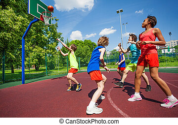 Teenagers in colorful uniforms playing basketball game on ...