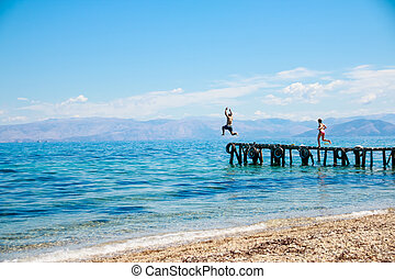 teenagers jumping off the pier into the sea. fun summer vacation.Young man jumps into the blue water from pier. View in motion.Happiness, summer, fun.Copy space