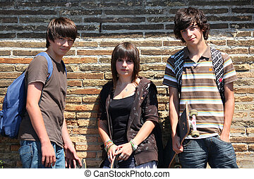 Teenagers leaning against a wall