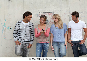 Teenagers leaning on city wall