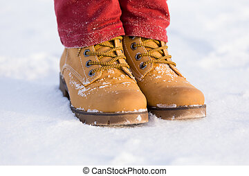Teenager's legs at the yellow boots on the snow