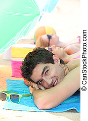 Teenagers lying on the beach