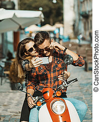 Young attractive couple of teenagers wears sunglasses on retro motorbike makes selfie, sunny street, urban hipster concept
