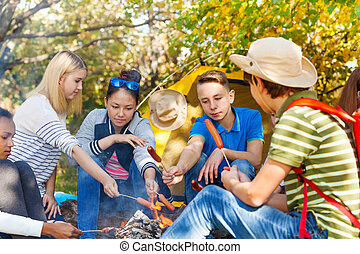 Teenagers on campsite grill sausages near fireplace with yellow tent during autumn day in the forest