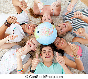 Teenagers on the floor with a terrestrial globe in the ...