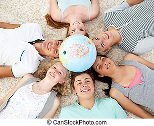 Teenagers on the floor with a terrestrial globe in the center of their heads