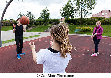 Teenagers playing basketball in park