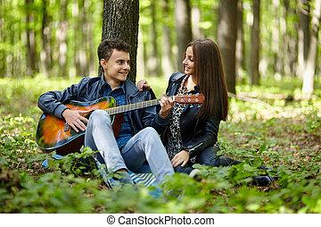 Teenagers playing guitar