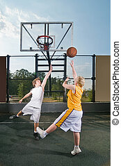 Teenagers playing streetball - Two teenagers playing...