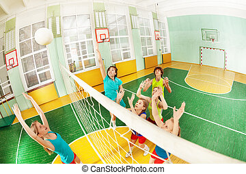 Teenagers playing volleyball in school gymnasium