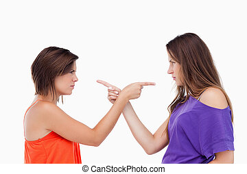 Teenagers pointing fingers on each other - Two teenagers...