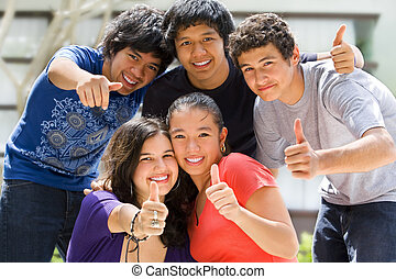 Multi ethnic teenagers posing outside school building