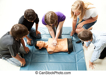 Teenagers Practice CPR - Teenage students use a mannequin to...