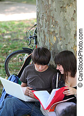 Teenagers sitting against a tree trunk and talking