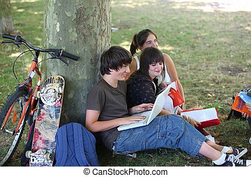 Teenagers sitting at the foot of a tree