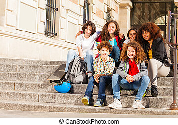 Teenagers sitting together on the steps outdoors