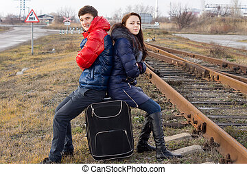 Teenagers sitting waiting at the side of a track