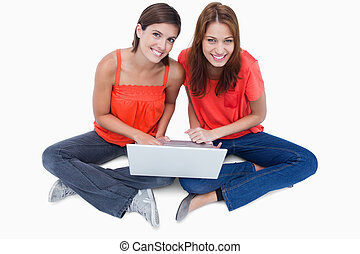 Teenagers sitting with a laptop on legs while looking at the camera and beaming