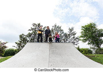 Teenagers standing on a halfpipe - Three friends standing at...