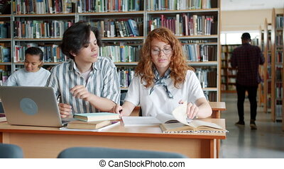 Teenagers studying in library using laptop reading books talking cooperating